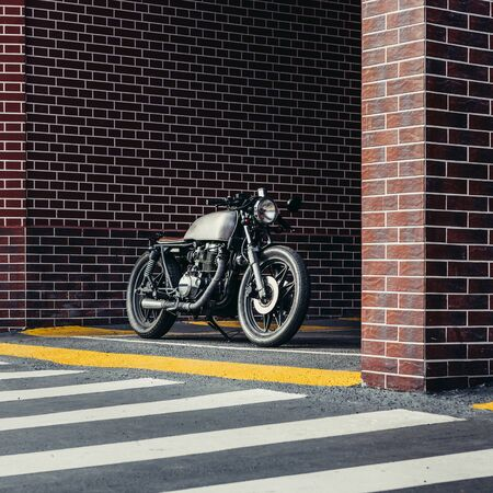 Handmade motorcyle parking near brick wall of industrial building. Everything is ready for having fun after hard day in office. Businessman city hipster hobby. Space for your individual text.