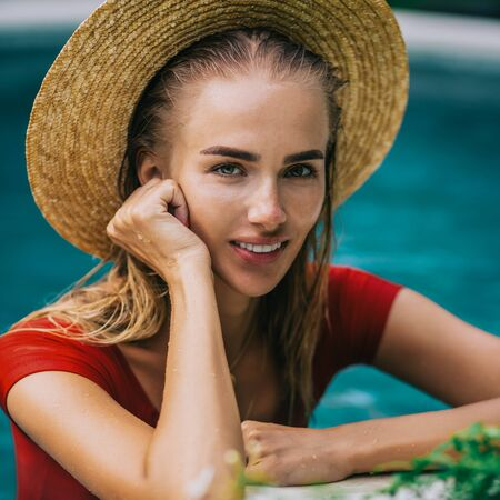 Closeup portrait of a beautiful young female in sexy red swimsuit and vintage straw hat posing in blue pool water. Hot sunny day. Tropic island vacation. Summer travel girl, active hipster lifestyle. Stock Photo