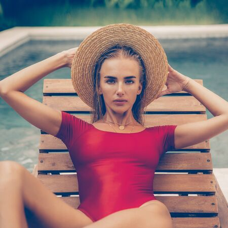 Close up portrait of a beautiful young lady in sexy red swimsuit and vogue vintage straw hat on lounger near pool. Hot sunny day. Tropic island vacation. Summer travel girl, active hipster lifestyle.