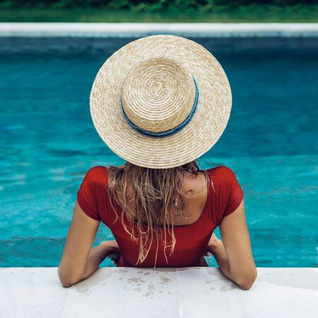 Back of a beautiful young woman in sexy red swimsuit and vintage straw hat posing in blue pool water. Hot sunny day. Tropic island vacation hotel. Summer travel girl, active hipster lifestyle.