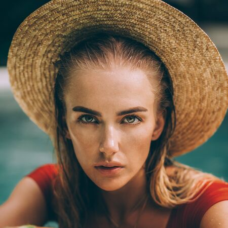 Closeup portrait of a beautiful young woman in sexy red swimsuit and vintage straw hat posing in blue pool water. Hot sunny day. Tropic island vacation. Summer travel girl, active hipster lifestyle. Stock Photo