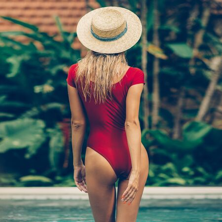 Fashion portrait of a beautiful young woman in sexy red swimsuit and vintage straw hat standing in pool. Hot sunny day. Tropic island vacation. Summer travel girl, active hipster lifestyle. Stock Photo