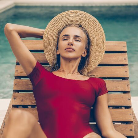 Close up portrait of a beautiful young woman in sexy red swimsuit and vogue vintage straw hat on lounger near pool. Hot sunny day. Tropic island vacation. Summer travel girl, active hipster lifestyle.