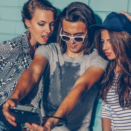 Ritratto di stile di vita di bellissimi hipster del migliore amico che indossano abiti eleganti e luminosi e si divertono. Bel ragazzo con due belle ragazze che prendono la foto dell'autoritratto selfie con la cinepresa davanti al mattone blu.
