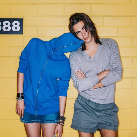 Young modern happy couple in love having fun in front of yellow brick wall. Beautiful lady in blue hoodie zipped all way up lay her head to her handsome husband shoulder. Man with crossed arms looks to the camera. Stock Photo