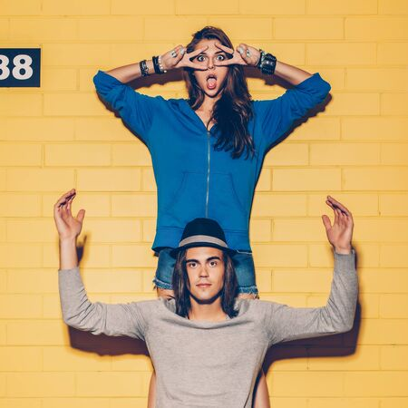 Young modern happy couple in love having fun in front of yellow brick wall. Beautiful longhaired girl in blue hoodie make mask with her fingers and her handsome husband rise his nads up. Boy sit on his skateboard.