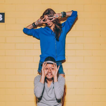 Young modern happy couple in love having fun in front of yellow brick wall. Beautiful longhaired woman in blue hoodie grimace and her handsome husband in hat hold his fingers as mask. Man sit on his skateboard.