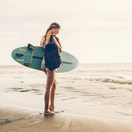 Young surfer girl in sexy white bikini with surf board and travel backpack walk on sunset beach. Modern family lifestyle, people water sport adventure camp and extreme swim on summer vacation Stock Photo