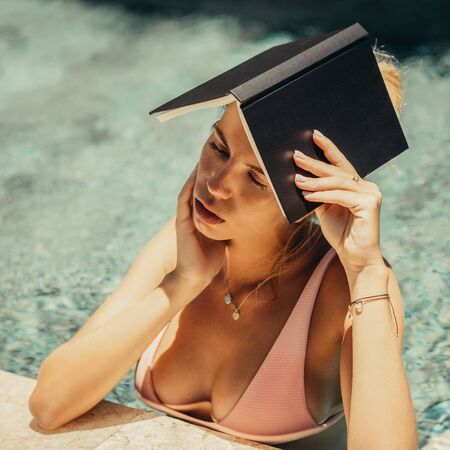 Beautiful woman in sexy pink bikini at the edge of a pool spa hotel make shadow with a book. Tropic island relax vacation concept. Summer idyllic travel girl, active hipster lifestyle advertising. Stock Photo