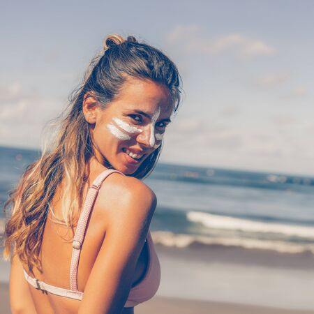 Portrait of a beautiful young female in pink bikini with white lines mask on her pretty face. Modern active lifestyle, people water sport adventure camp and extreme swim on summer vacation.