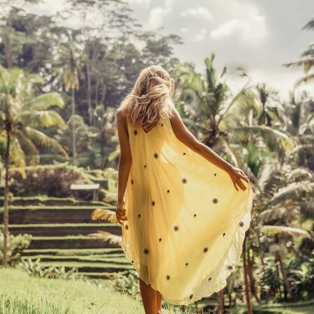 Beautiful young woman in yellow silk dress. Girl travel and explore world. Typical Asian hillside with rice farming, mountain shape green cascade rice field terraces paddies. Ubud, Bali, Indonesia.