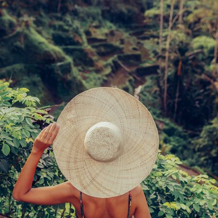 Beautiful young woman in straw hat travel and explore world. Girl look at typical Asian hillside with rice farming, mountain shape green cascade rice field terraces paddies. Ubud, Bali, Indonesia. Stock Photo
