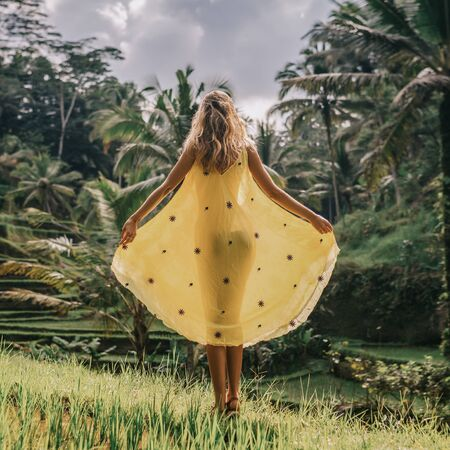 Beautiful young female in yellow silk dress. Girl travel and explore world. Typical Asian hillside with rice farming, mountain shape green cascade rice field terraces paddies. Ubud, Bali, Indonesia.