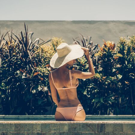 Beautiful young slim woman in sexy pink bikini and straw hat sit on edge of swimming pool spa. Tropic island relax vacation concept. Summer idyllic travel girl, active hipster lifestyle advertising. Stock Photo