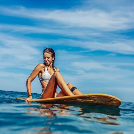 Beautiful fit surfing lady in sexy bikini doing yoga on big longboard surf surfboard board on sunrise or sunset in the ocean and try to find balance. Modern active sport lifestyle and summer vacation.
