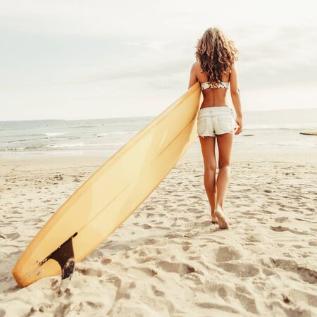 Rear view of beautiful surfing girl in sexy short shorts with sporty ass hold yellow surf longboard surfboard board on a beach at sunset or sunrise. Modern active sport lifestyle and summer vacation.