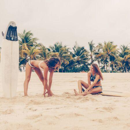 Zwei surfendes Mädchen mit Shortboard-Surfbrett-Surfbrett im Bikini an einem Strand, der sich ausdehnt, bevor er bei Sonnenaufgang oder Sonnenuntergang zu den großen Meereswellen geht. Moderner aktiver Sportlebensstil und Sommerurlaub.