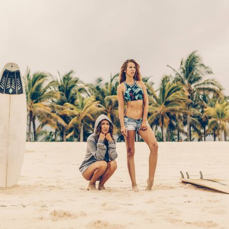 Two beautiful girl in shorts come to see ocean before go to lineup with wooden surf white surfboard board at sunrise or sunset on a sand beach. Vacation concept. Summer holidays. Tourism, sport. Stock Photo