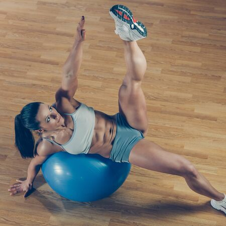 Beautiful athletic trainer shows examples of exercises in the gym 免版税图像