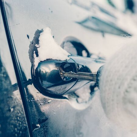 Young beautiful woman in pretty white knitted mittens try to open vehicle on a winter morning. Close-up of a key inserted into the lock of frozen car door. Transportation and ownership concept.