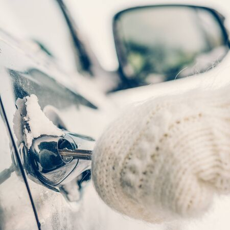 Young beautiful girl in hipster white knitted mittens try to open vehicle on a winter morning. Close-up of a key inserted into the lock of frozen car door. Transportation and ownership concept.