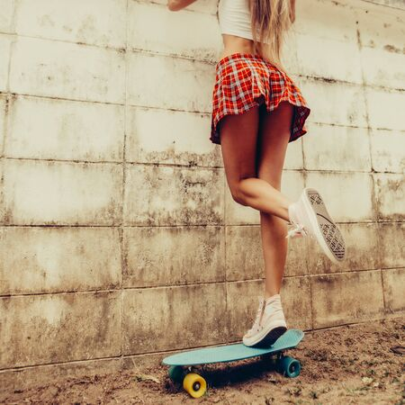 Sporty young woman with fit butt in a red tartan mini skirt stands on blue penny skateboard trying to look over the fence of a tropical garden. Outdoor lifestyle picture on a sunny summer day.
