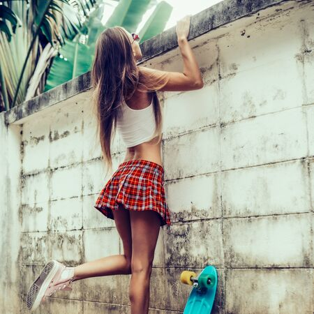 Skinny young girl with sporty butt in a red tartan mini skirt with blue penny skateboard trying to climb over the fence of a tropical garden. Outdoor lifestyle picture on a sunny summer day.