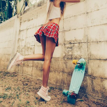 Athletic young girl with fit butt in a red tartan mini skirt with blue penny skateboard trying to climb over the fence of a tropical garden. Outdoor lifestyle picture on a sunny summer day.