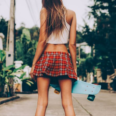 Skinny young woman with fit in a red tartan mini skirt with blue penny skateboard shortboard stands on the tropical street. Outdoor lifestyle picture on a sunny summer day.