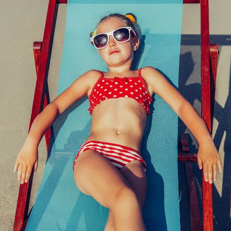 Cute little girl in red swimsuit and sunglasses enjoying on a sun lounger rest on the beach chair on tropical sandy beach sea shore. Sunbathing and leisure on sunny day.