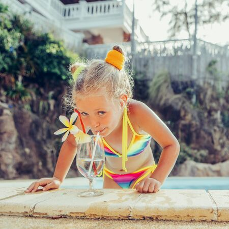 Cute little blonde girl swimming in big pool. Big glass with water, straw and frangipani stay on the pool edge. Little lady smile and drink from the glass. Sunbathing and leisure on sunny summer day.