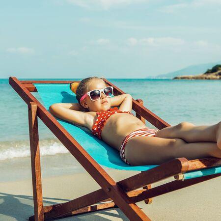 Niño lindo en traje de baño rojo y gafas de sol blancas disfrutando de una tumbona descansando en la silla de playa en la orilla del mar de la playa de arena tropical. Tomar el sol y ocio en un día soleado.