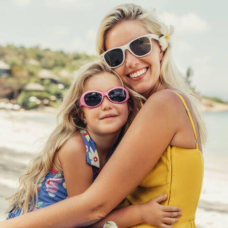 Outdoor-Porträt der schönen blonden Mutter und ihrer süßen Tochter. Kleines Mädchen und ihre Mama schauen in die Kamera am Strand. Kleine Dame und Mutter mit Sonnenbrille. Sonniger Sommertag Glücklicher Muttertag. Standard-Bild