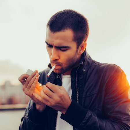 Close up portrait of a handsome rider guy with beard and mustache in black biker jacket, white t-shirt and fashion sunglasses light up cigaret on rooftop at sunset. Brutal fun urban lifestyle. Stok Fotoğraf