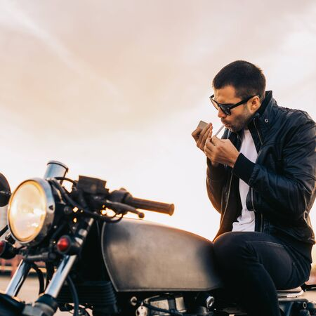 Handsome rider male with beard and mustache in black biker jacket and fashion sunglasses smoke cigaret and sit on classic style cafe racer motorbike on rooftop at sunset. Brutal fun urban lifestyle.