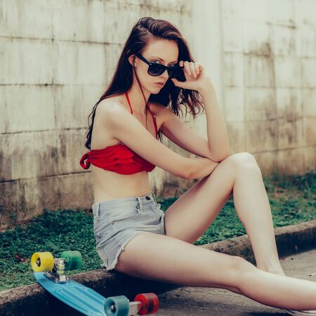 Pretty beautiful woman in red bra bikini, white sneakers and short denim shorts sit with short skate board. Urban scene, city life. Cute attractive sexy hipster lady look over her trendy sunglasses. Banque d'images
