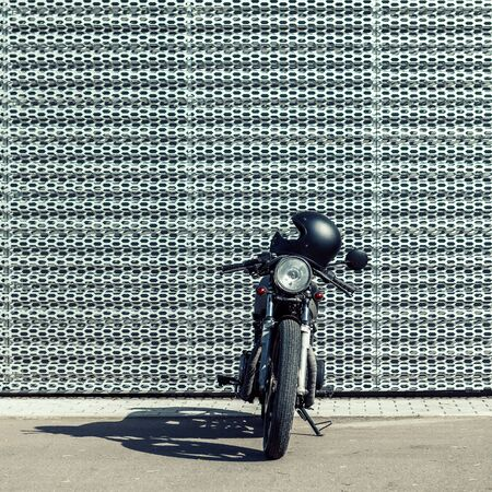 Custom motorcycle parking near wall of finance building. Everything is ready for having fun driving the empty road on a motorcycle tour journey. Businessman hobby. Space for your individual text.