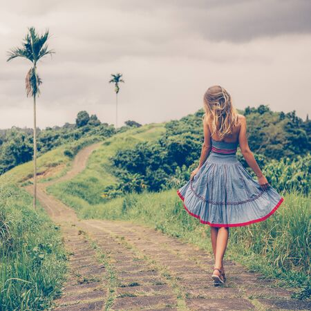 Beautiful young woman in blue vintage dress dance at stone hill path in Asia. Girl travel and explore world. Long lonely road in mountains. Travel and adventure mockup. Romantic scene concept. 免版税图像