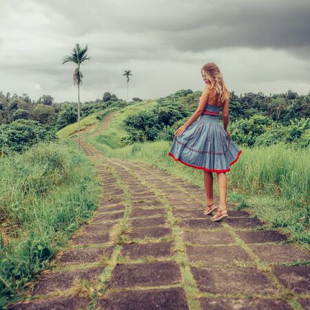 Beautiful young woman in blue vintage dress have fun at stone hill path in Asia. Girl travel and explore world. Long lonely road in mountains. Travel and adventure mockup. Romantic scene concept.