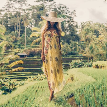Beautiful young female in shine through dress and straw hat. Girl walk at typical Asian hillside with rice farming, mountain shape green cascade rice field terraces paddies. Ubud, Bali, Indonesia. 免版税图像