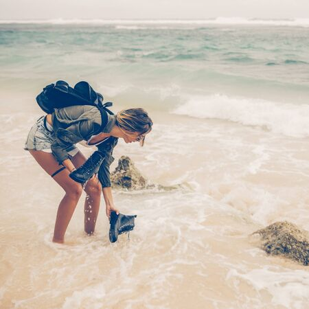 Hipster fit woman in sexy shorts, khaki shirt, sunglasses and travel backpack catch her army boots in ocean. Modern tourist traveler, active lifestyle, sport adventure camp and extreme on vacation.