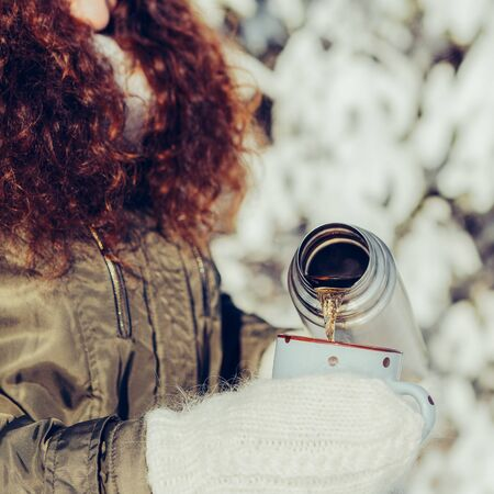 Young beautiful woman in hipster white knitted mittens drink hot tea on a bright winter day. Close-up of a cup filled with hot liquid. Trees in pure first snow on a background. 免版税图像