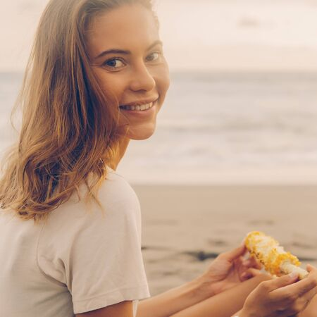 Healthy diet. Vegetarian hipster girl eat fresh organic grilled corn and look to camera. Sporty lady on sea beach sunset or ocean sunrise. Travel, active, yoga, vegan and dieting lifestyle concept. 免版税图像