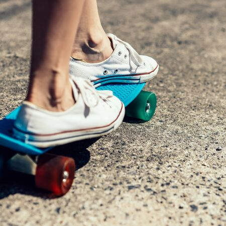 Close up of feet of a beautiful woman in white trendy sneakers rides on blue penny skateboard longboard with multi colored wheels. Urban scene, city life. Sport. Cute hipster lady have fun. Sunny day. 免版税图像