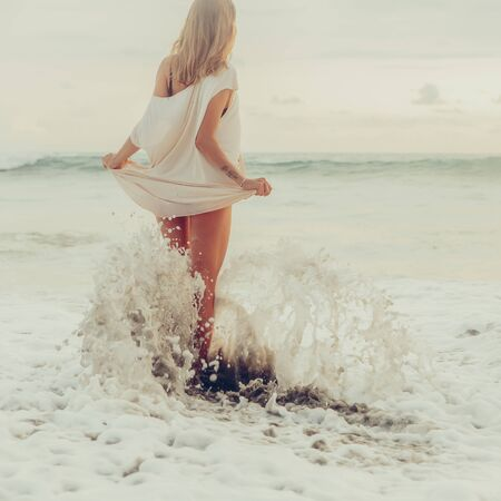 Hipster trendy woman hold her long summer dress and bikini trying not to wet it in waves. Sporty fit lady on sea sand beach sunset or ocean sunrise. Travel, active, yoga, freedom lifestyle concept.