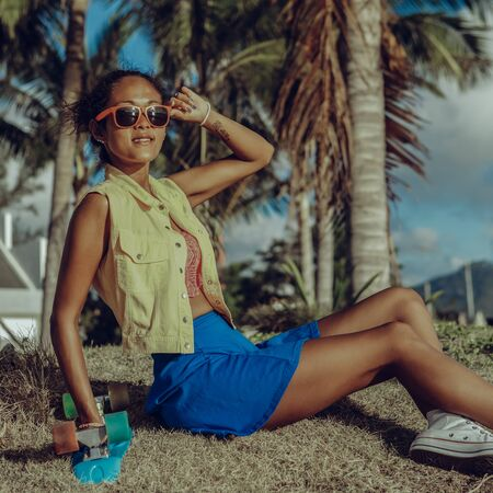Outdoor lifestyle portrait of beautiful black female in bright outfit and sunglasses. Hipster woman with her penny skateboard sit at dry grass under palm tree. Sunny summer hot day. Swag, fashion.