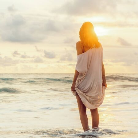 Hipster girl after hot summer day hold her long light dress trying not to wet it in cool water. Fit lady in sand sea beach sunset or ocean sunrise. Travel, active, yoga, freedom lifestyle concept. 免版税图像