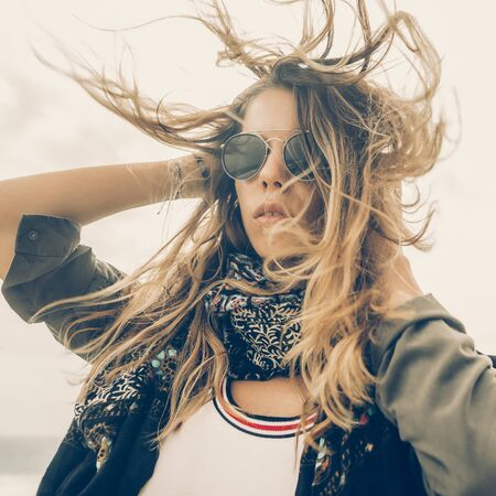 Hipster woman in fashion khaki shirt vogue scarf and vintage sunglasses correct her long hairs on the wind . Modern tourist traveler, active lifestyle, sport adventure camp and extreme on vacation. 免版税图像