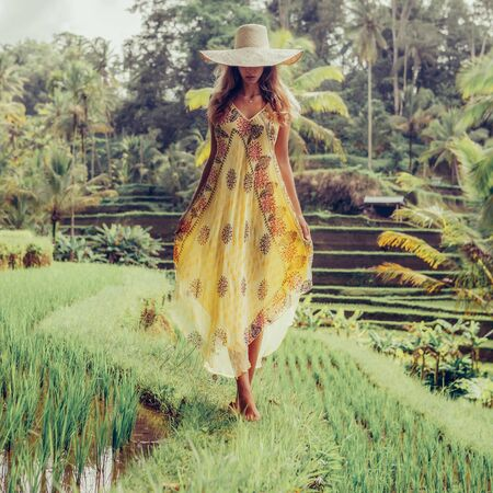 Beautiful young lady in shine through dress and straw hat. Girl walk at typical Asian hillside with rice farming, mountain shape green cascade rice field terraces paddies. Ubud, Bali, Indonesia. 免版税图像