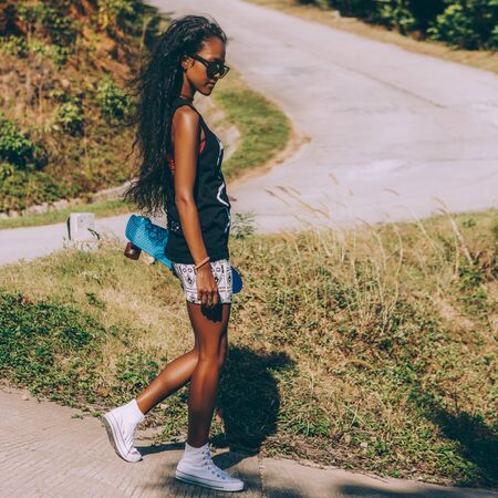 Outdoor lifestyle portrait of beautiful teenage black girl with curly hair. Woman walks in front of danger mountain road with her penny longboard skateboard. Freedom, challenge, doubt and happiness.